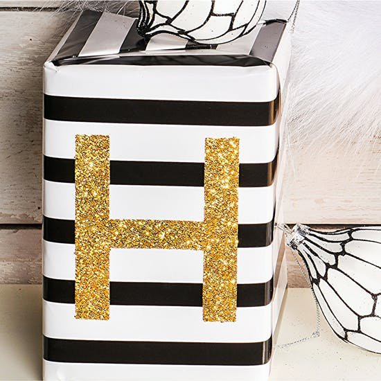 Glittery Gold Giant Letter Sticker on a black and white gift wrapped present