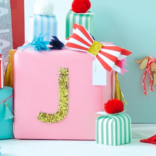 Giant Gold Letter Sticker 'J' on a pink gift