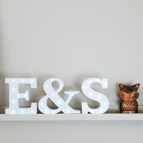 Lifestyle image of white light up letters on a shelf spelling E & S